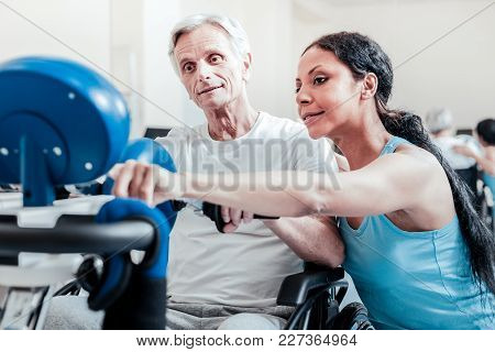 Active Lifestyle. Alert Old Grey-haired Man Exercising On A Training Device And Sitting In A Wheelch
