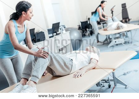 Being A Trainer. Concentrated Old Grey-haired Crippled Man Lying On Bed While A Concentrated Young D