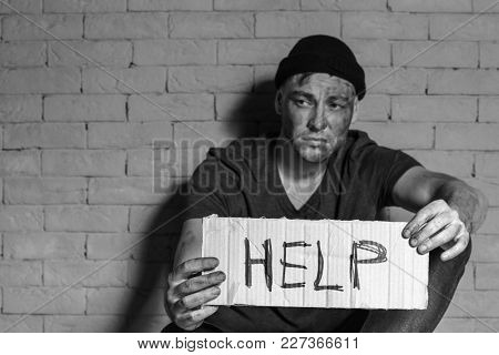 Homeless poor man holding carton board with word HELP while sitting near brick wall