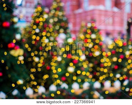 Christmas Blurred Image Of Decorated Spruce In Street On Background Of Building.
