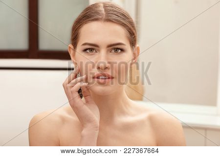 Young woman with beautiful eyebrows indoors
