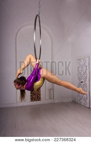 Beautiful Aerialist Girl Doing Acrobatic And Flexible Tricks On Aerial Ring (lyra) In Photostudio Wi
