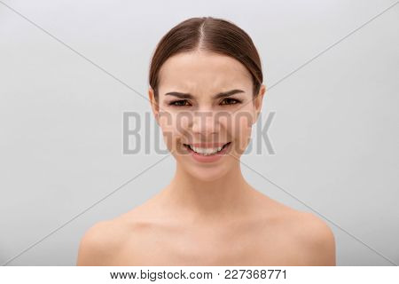 Emotional young woman frowning eyebrows on light background