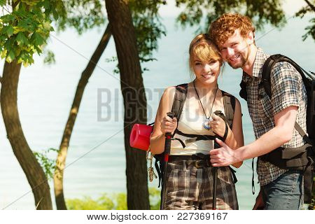 Two Young People Tourists Hiking By Sea Ocean Water. Backpackers Couple On Summer Vacation Trip Jour