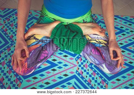 woman legs in colorful leggings in lotus pose from above view indoor shot