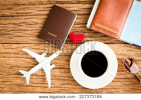 Passport And Black Coffee And A Wallet And A Plane Model And Red Heart And Map Put On The Wood Textu
