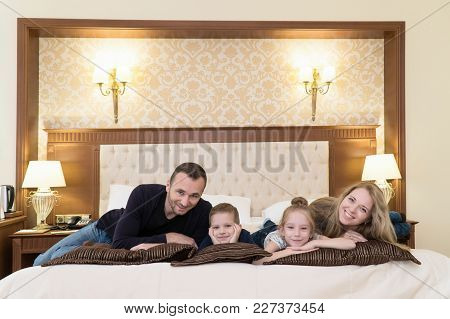 A Happy Family Posing On Camera In Hotel Room Sitting On Bed.