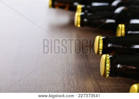 Fresh beer in glass bottles on wooden background, closeup