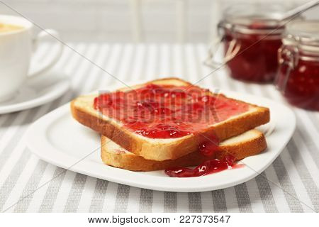 Delicious toast with sweet jam served for breakfast on table