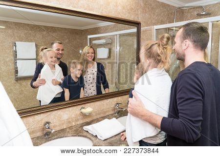 The Husband, Wife And Children Stand In Front Of The Mirror In The Bathroom Of The Hotel Room And Sm