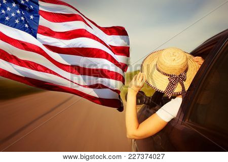 Traveling in America concept - Young woman in car and american flag. Freedom, travel and vacation, road trip concept