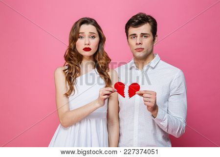 Photo of young sad loving couple standing isolated over pink background holding broken heart. Looking camera.