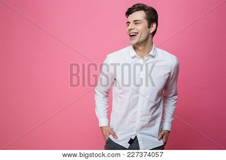 Photo of young happy man standing isolated over pink background. Looking aside.