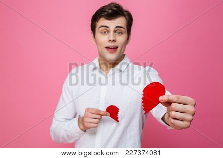 Photo of young man standing isolated over pink background give you a two halves of heart. Looking camera. Focus on heart.