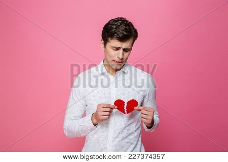 Photo of young sad man standing isolated over pink background holding broken heart. Looking aside.