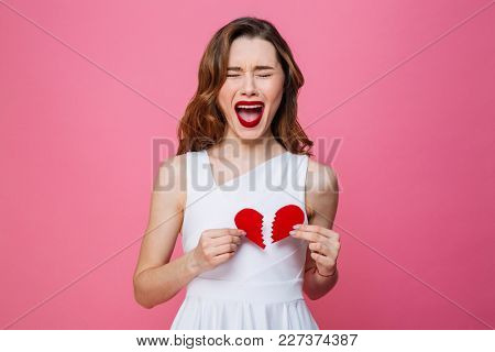 Photo of young screaming woman standing isolated over pink background holding broken heart.
