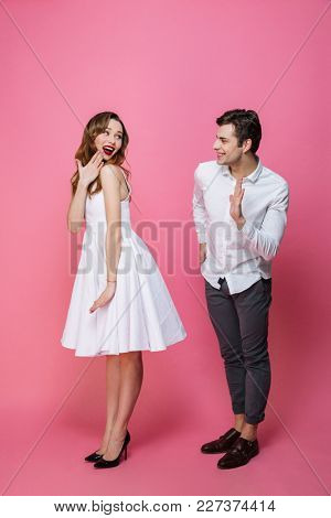 Image of young amazing loving couple standing isolated over pink background. Looking at each other.