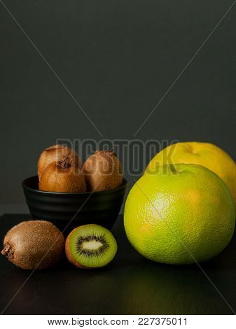 Few Kiwi In Black Plate And Sweetie Still Life On Dark Background. Food Photo With Citrus And Sliced