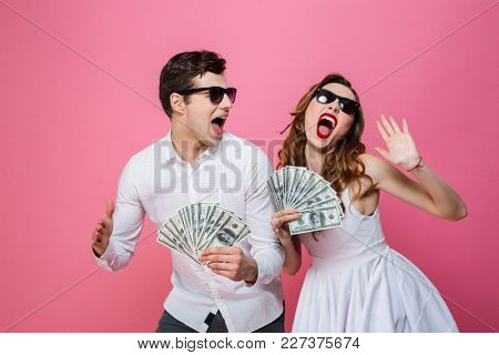 Portrait of an excited smartly dressed couple holding bunch of money banknotes and celebrating isolated over pink background