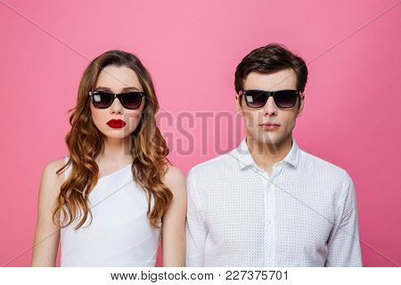 Photo of young serious loving couple standing isolated over pink background wearing sunglasses.
