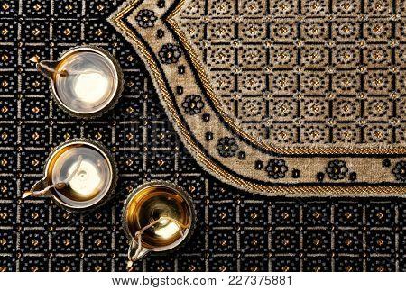 Diwali diyas or clay lamps on ornate fabric