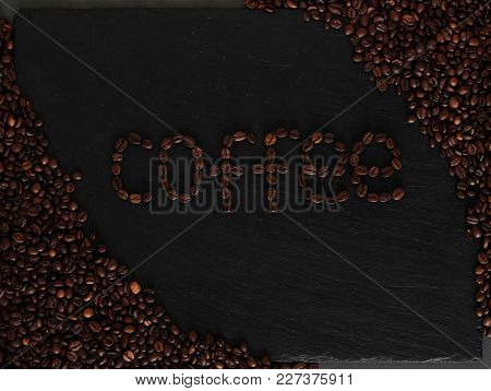 Dark Background With Coffeeped Phrase Coffe. Black Texturised Background With Coffee Beans.