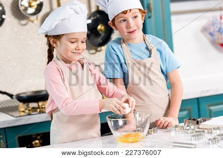 Cute Little Siblings In Chef Hats And Aprons Preparing Dough Together In Kitchen