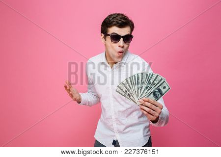 Photo of young excited man standing isolated over pink background wearing sunglasses holding money.