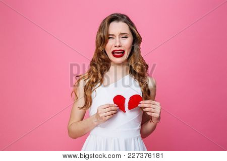 Image of young sad woman standing isolated over pink background holding broken heart. Looking camera cries.
