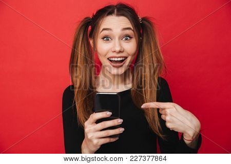 Photo of young cute excited lady standing isolated over red background chatting by mobile phone. Looking camera pointing.