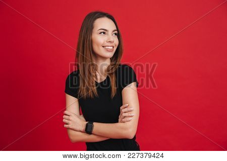 Portrait of a happy casual girl standing with arms folded and looking away at copy space isolated over pink background