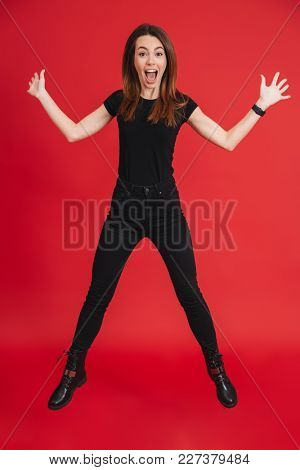 Full length of an excited casual girl jumping and having fun isolated over pink background