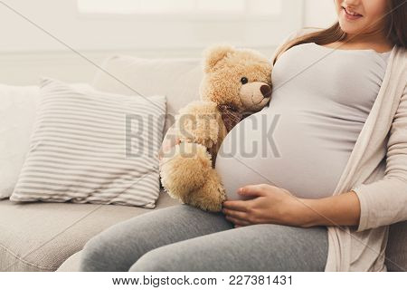 Pregnant Woman Holding Teddy Bear At Her Tummy, Unrecognizable Expectant Lady Sitting On Sofa With N