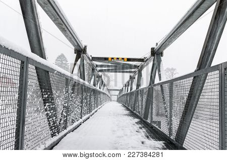 Pedestrian Metal Bridge In Winter, Snow In The Air And On The Bridge. Foss Bridge Is Crossing The To