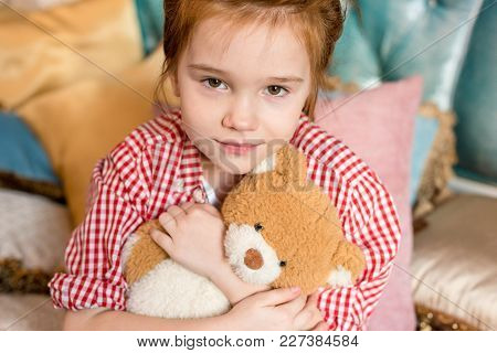 Cute Little Child Hugging Teddy Bear And Smiling At Camera