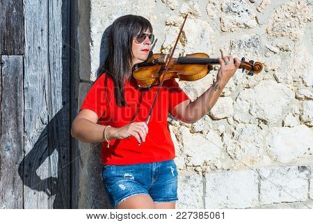Woman Playing Violin In Studio With White Background. With Red Dress. A Classic Musical Instrument F