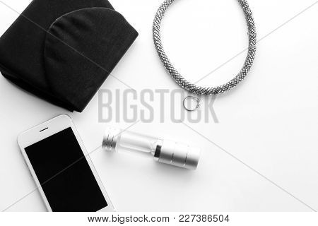 Bottle of perfume, smartphone and necklace on white background
