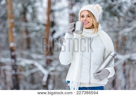Selective Focus Of Young Woman Drinking Hot Tea From Thermos In Winter Forest