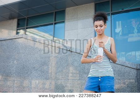 Young African-american Woman Runner Is Having Break, Drinking Water While Jogging In City Center