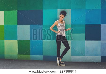 Tired African-american Woman Leaning On Bright Blue Graffiti Wall, While Listening Music, Relaxing F