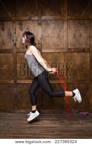 Girl In Grey T Shirt And Black Leggins. Jumping On Rope.