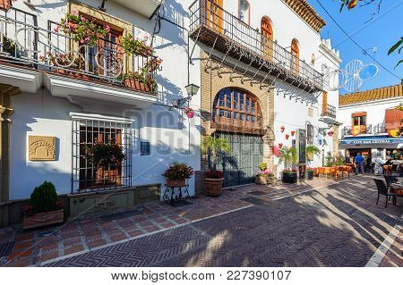 Marbella, Spain - December 2017: Traditional Spanish Narrow Street With Souvenir Shop And Beautiful