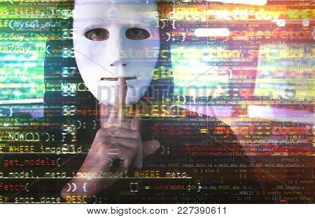 Hacker in mask showing silence gesture and code on blurred background. Concept of cyber attack and security
