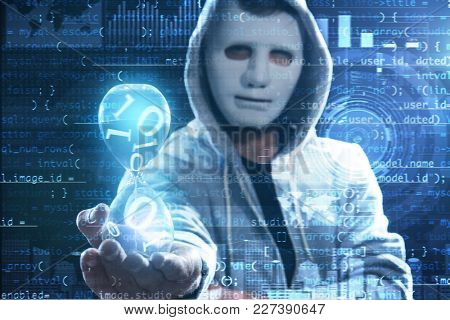 Hacker in mask holding hourglass and code on dark background. Concept of cyber attack and security