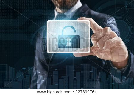 Businessman holding virtual icon with lock on dark background. Concept of cyber attack and security