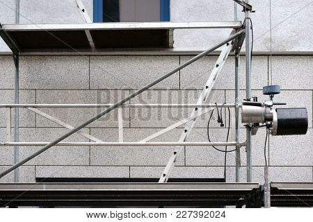 The Close-up Of A Goods Lift Next To The Scaffolding Of A Construction Site.