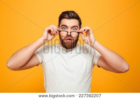 Portrait of a surprised bearded man in eyeglasses looking at camera isolated over yellow background