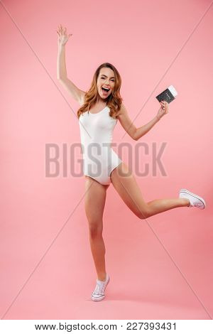 Full-length photo of beautiful woman in white swimsuit rejoicing vacation with passport and tickets in hand, isolated over pink background
