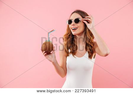 Sexual pleased woman with brown hair in swimsuit and sunglasses smiling and holding cocktail from coconut, isolated over pink background
