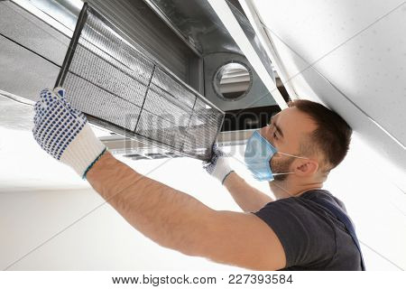 Male technician cleaning industrial air conditioner indoors